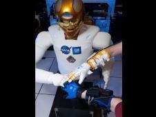 Robonaut and Robo-Glove Commander Dan Burbank works with Robonaut 2. The robot humanoid demonstrated its dexterity performing sign language. Credit: NASA TV