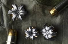 these flower-like pieces of jewelry are created from bullet fragments from shooting guns underwater