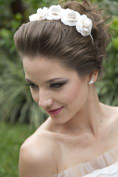 Tiara Marina em um lindo penteado para noivas, com delicadas camélias feitas em cetim R$ 270,00.  Brinco Eduarda: de prata e zircônias em formato de meio lua R$ 365,00.