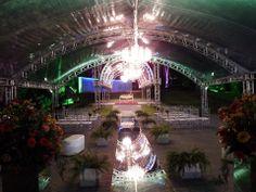 Cerimonia externa com lustres de cristal, verdes e passarela espelhada e muita iluminação