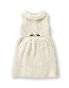 Darling sweater dress in soft acrylic features allover texture and cable-knit bodice. Faux-leather trim and gold-tone bridle bit accent add countryside style.