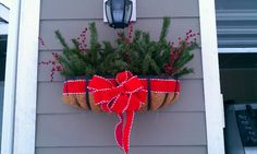 Easy Christmas flower box decor. I just used an old fake tree and some fake berry sprigs that I picked up at Joann's with some red ribbon. Very nice and easy to do.