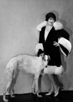 Model wearing fashionable fur-trimmed coat with Russian Wolfhound dog at her side, 1929