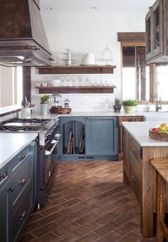 Farmhouse kitchen with a farmhouse sink, white backsplash, terra-cotta floors, open cabinets and beige cabinets.