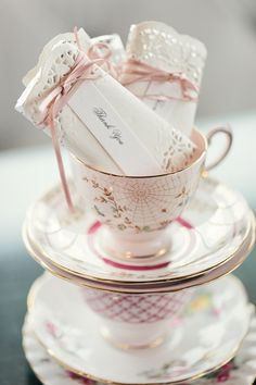 "Notice the little paper doily wrapped gift with name resting in the tea cup.  what a sweet idea. these little ""packages"" would also act as name cards."