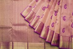 A purple and gold Kanjivaram adorned with exquisite paisleys in the body of the sari.