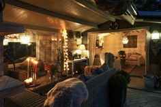 Cozy outdoor living room, hanging lights, candles, blankets