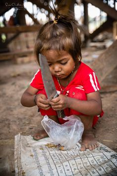 Cambodian Children: full of life, tenacious and extremely resourceful ~ this little girl is cutting open her snack of nuts ~ Susan Crichton-Stuart