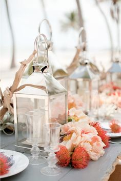 Stunning table scape a seaside theme with Lanterns, coral colored Peonies & other flowers.