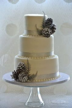 This a very small wedding cake (4, 6, and 8 inch) iced with vanilla buttercream, decorated with ribbon and pinecones.