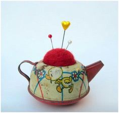 would love to find an old tin teapot from doll dishes set to make a sweet little pincushion like this!!