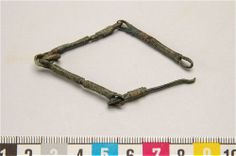 Viking Age bronze Chain; Gotland; Four links of a chain,  where each link is wrapped in bronze wire, and a loop attaches each link to the next link.