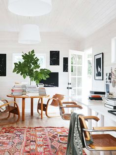 Bright and colorful studio office workspace with entry table piled with books and white-washed ceiling on Thou Swell @thouswellblog