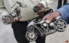 Visitors hold metallic abstracts of motorcycles displayed at an exhibition in Bangalore, India, Thursday, Nov. 20, 2008. The abstracts and sculptures created by an artist Ilyas Ahmed, unseen, made of metal scrap, mostly of automobile parts are priced between USD $40 and 1,000. (AP Photo/Aijaz Rahi)