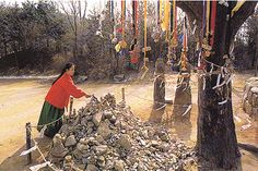 In South Korea, a young woman adds a stone to a rock pile for good luck. In some mountain areas, small piles of stones can be seen near temples, ancient trees, waterfalls and other sacred places. A visitor may add a stone to a pile or tie a piece of colored cloth to a tree branch as an offering to the local spirit, such as the Mountain God.