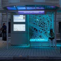 the futuristic bus stop for gare de lyon has been developed to fit the needs of the century parisian, outfitted with time-indicating lighting, a bike docking station, lending library, ticket office and interactive touch screens. Urban Furniture, Street Furniture, Bus Stop Design, Ligne Bus, Paris, Bus Shelters, Shelter Design, Bus Station, Train Station
