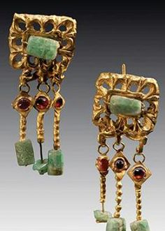 PAIR OF ROMAN GOLD, EMERALD, AND GARNET EAR PENDANTS from which hang three gold…