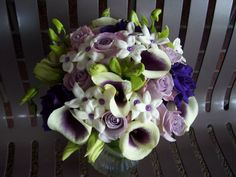 Close up of the Brides bouquet with Piscasso calla lilies, lime small orchids, lavender roses, purple lizanthis, stephanotis with purple centers www.artisticfloraldesign.com