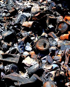Photo of a heap of burnt out paint cans found in junk yard