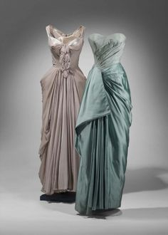 Evening dress of gray pearl silk chiffon over silk satin. Bodice has wide straps and draped chiffon forming decorative element on center front. Skirt has draped chiffon swagged around hips and brought to back in seam.