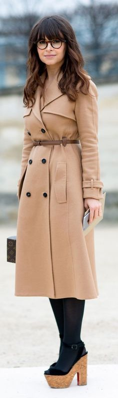 Paris Fashion Week street style: MIroslava Duma wearing a belted camel coat with black tights and platform sandals with a Louis Vuitton bag and clear glasses