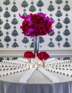 Before entering the reception space, guests found their table assignments on a table covered with a shimmering silver linen. A large mercury-glass vase in the center of the table was filled with red roses and fuchsia phalaenopsis orchids. #placecardtable #centerpiece Photography: Embrace Life Photography. Read More: http://www.insideweddings.com/weddings/santa-monica-poolside-wedding-with-a-modern-tropical-feel/548/