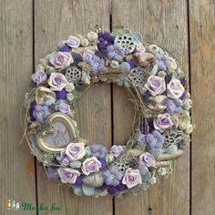 Romantikus ajtódísz lila színben. A széles, lapos formájúra készített koszorúalapomat először textillel vontam be, majd hamvasított lótusszal, kecskerágó termésekkel, és nyírfa ágakkal borítottam. A termések közötti részeket natúr és menta színű izlandi zuzmóval töltöttem ki. A lila több árnyalatában viruló habrózsákkal és saját készítésű horgolt virágokkal díszítettem, amiket hamvas mű menta levelekkel és lila gyapjú golyókkal egészítettem ki. Egy szív formájú antik hatású kis képkeretet is…