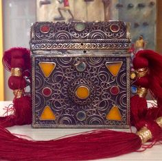 This is the front view of a small and wonderful antique Quran book box crafted in extensively worked metal and set with resin and coloured stones.  Our Client added the red silk cord