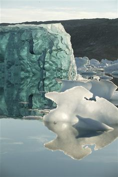 An iceberg made of densely formed ice, shows light transmitted through it.   Photographer: Greenpeace / Nick Cobbing