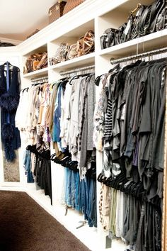 Khloe Kardashian's closet, luggage on top of closet, bags on top, clothes color coordinated, pants on bottom, black hangers
