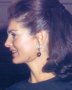 Jacqueline Bouvier Kennedy wearing the pearl and diamond earrings that she received as a gift from her husband for their first wedding anniversary. They had interchangeable black and white pearl drops made by Camrose & Kross.