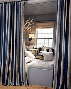 Reading nook in blue and white, white antlers, rustic flooring, wall-mounted sconce