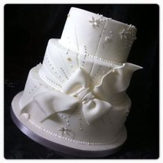 All white wedding  cake with large bow and edible silver and ivory pearls.