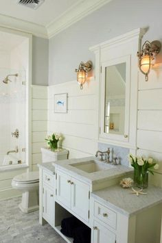 source: Jillian Klaff Homes      Cottage bathroom with gray paint color paired with white tongue and groove walls and white bathroom crown molding. Ivory framed inset medicine cabinet framed by nickel marine sconces paired with white bathroom vanity with marble countertop and nickel vintage bathroom faucet. White wood paneled drop-in tub and white carrara marble tiles floor.