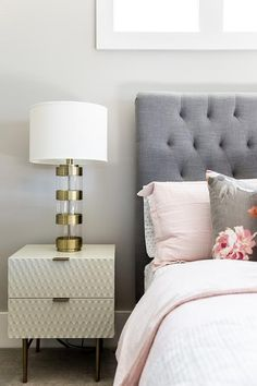 A West Elm Audrey Nightstand sits on a gray rug and is topped with a glass and brass ring lamp placed in front of a light gray wall beside a bed dressed in a light pink duvet paired with a gray and pink floral print pillow layered in front of pink shams placed against a gray tufted headboard.