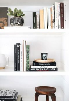 Styled bookshelves with plants, books, and objects.