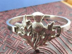 lovely Scottish Thistle bangle bracelet Beautiful Silver plated over brass with vintage pieces. Verbuni Designs Made in USA The lovely simple thistle, symbol for the mighty Scots! Elegant bold but a touch of strength Opens in front for ease of wear.