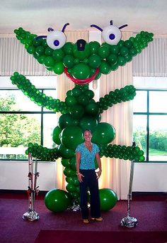 A balloon sculpture of a green monster. Floor to the ceiling. Must be bigger, but the ceiling is only 12'. By original design the monster suppose to have 6 hands - one for every hobby the kids had - it was double Bar/Bat Mitzvah. End up with just four, but just as happy!   Balloon decorations come small, medium and big.  This is a logo of a club, big balloon sculpture!   wowballoons.com