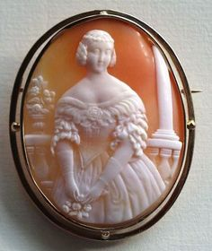 Cameo depicting a 3/4 frontal figure of a young lady posed against a background composed of a balustrade, an urn with flowers, and a pillar, mounted in 18K gold, France, 1850s.