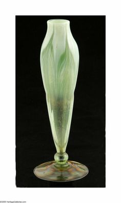 An American Art Glass Vase, Tiffany Studios, c.1900,  The iridescent floriform bud vase on a round gold foot highlighted with amber and green, the green,  transparent to opaque elongated vase with a green 'Pulled Feather' pattern, engraved signature,  underside L.C.T. W3175, 7.7in. high