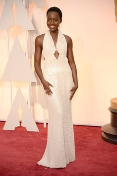 Lupita Nyong'o on the 2015 Oscar red carpet wearing a Calvin Klein gown, Chopard jewelry, and Nicholas Kirkwood shoes.