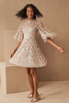 Densely embroidered with a pastel motif of birds and flowers, this feminine tulle mini features voluminous sleeves, frill trim, and a touch of beading for subtle sparkle.