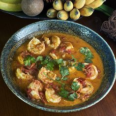 Burmese Shrimp Curry Generous 1 pound shrimp, peeled and deveined 1/4 cup minced shallots 1 small clove of garlic, peeled and minced 3 TBS peanut oil 1/8 tsp turmeric 1 1/2 cups chopped ripe tomatoes or canned crushed tomatoes 3/4 cup water 2 tsp fish sauce 2 green cayenne chiles, seeded and minced, or to taste 1/2 tsp salt, or to taste About 1/4 cup cilantro leaves (optional) 1 lime, cut into wedges (optional)
