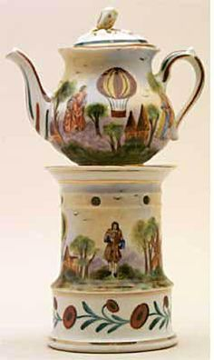 Teapot #379  Cylindrical, white background, paintings of windmill, a balloon, church, trees, a man and couple on stand, couple and woman on pot.  Acquired in Dijon