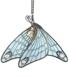 Art Nouveau Silver, Silver-Gilt, Plique-à-Jour Enamel, Moonstone and Opal Pendant with Antique Silver Slide Chain. Centring the profile of a fairy's silver-gilt visage surmounted by one small oval opal and a pair of intertwined antennae, draped by oversized wings fashioned of light blue plique-à-jour enamel, surmounted by 3 oval and round moonstones and marcasite arcs, circa 1890, with long silver slide watch chain. #ArtNouveau #pendant