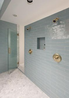 Amazing master bathroom features a glass shower door with brass handle which opens to a large shower clad in linear blue glass tiles lined with his and her shower heads as well as a carrera marble hex tiled shower floor. Glass Tile Shower, Blue Glass Tile, Shower Floor Tile, Shower Panels, Glass Tiles, Shower Niche, Hexagon Tile Bathroom, Marble Bathroom Floor, Small Bathroom