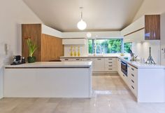 White cabinets with a touch of wood and polished beige tiles