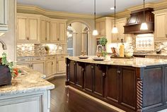 Kitchen Design Gallery | Marsh Kitchens, white cabinets, white granite, white, brown, grey tile backsplash, dark wood kitchen island, dark wood oven hood, open concept. hard wood floors