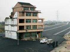 Een bejaard stel uit de Chinese stad Wenling heeft geweigerd om te verhuizen, toen er naast hun huis een nieuwe snelweg werd aangelegd. Nu staat hun woning in het midden van de straat.