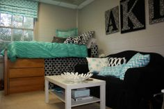 Teal, black and white single dorm room at Samford University. Love the large monogram wall art for a dorm and the chevron throw pillow on the couch.
